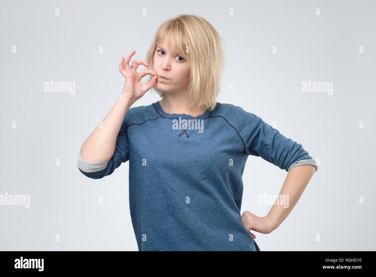 Keep a secret, woman zipping her mouth shut. - Stock Image