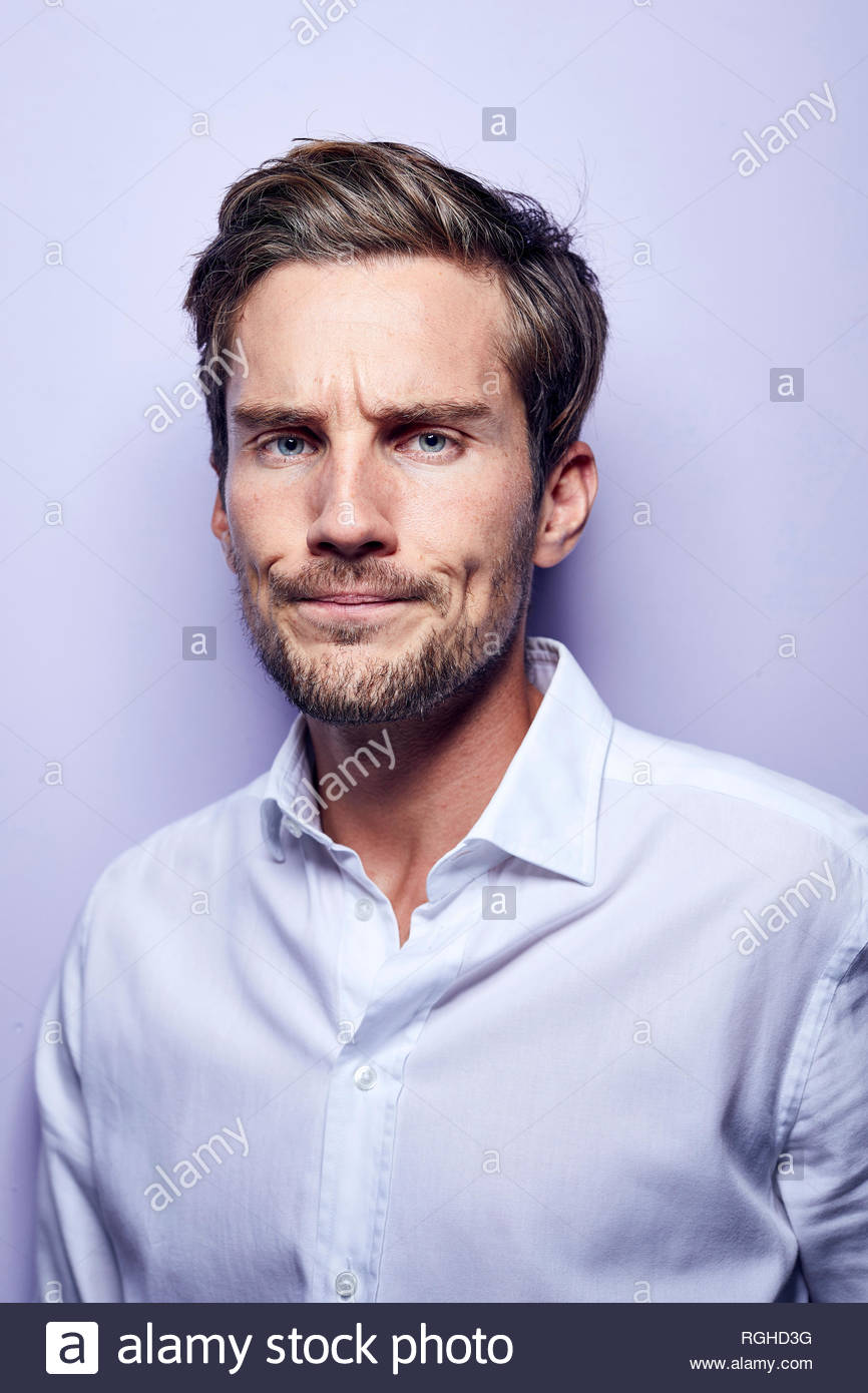 Portrait of critical young man in front of purple background - Stock Image