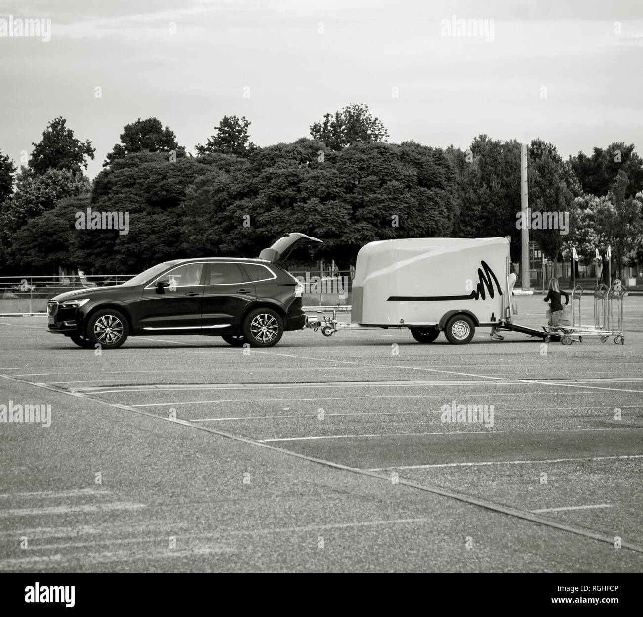 STOCKHOLM, SWEDEN - JUN 7, 2018: Single mother with her daughter loading in the Volvo SUV car trailer good bought from IKEA furniture store in the wide empty parked of the Swedish furniture retailer - black and white image - Stock Image