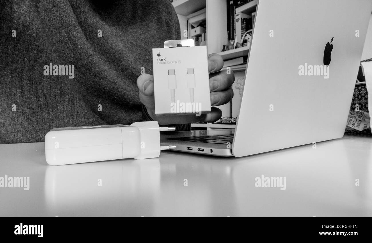 PARIS, FRANCE - FEB 23, 2018: Man unboxing Apple Computers USB-C charging cable bought to power the latest MacBook Pro laptop Stock Photo