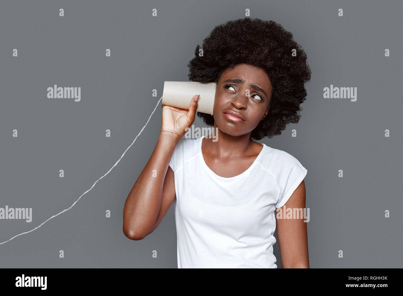 Young african woman standing isolated on gray wall listening conversation on paper cup telephone grimacing unsatisfied - Stock Image