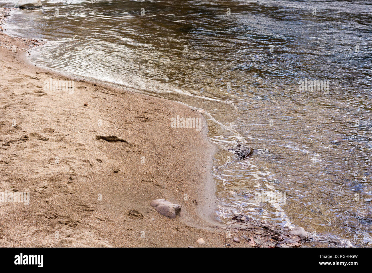 Water lapping onto sand, UK - Stock Image