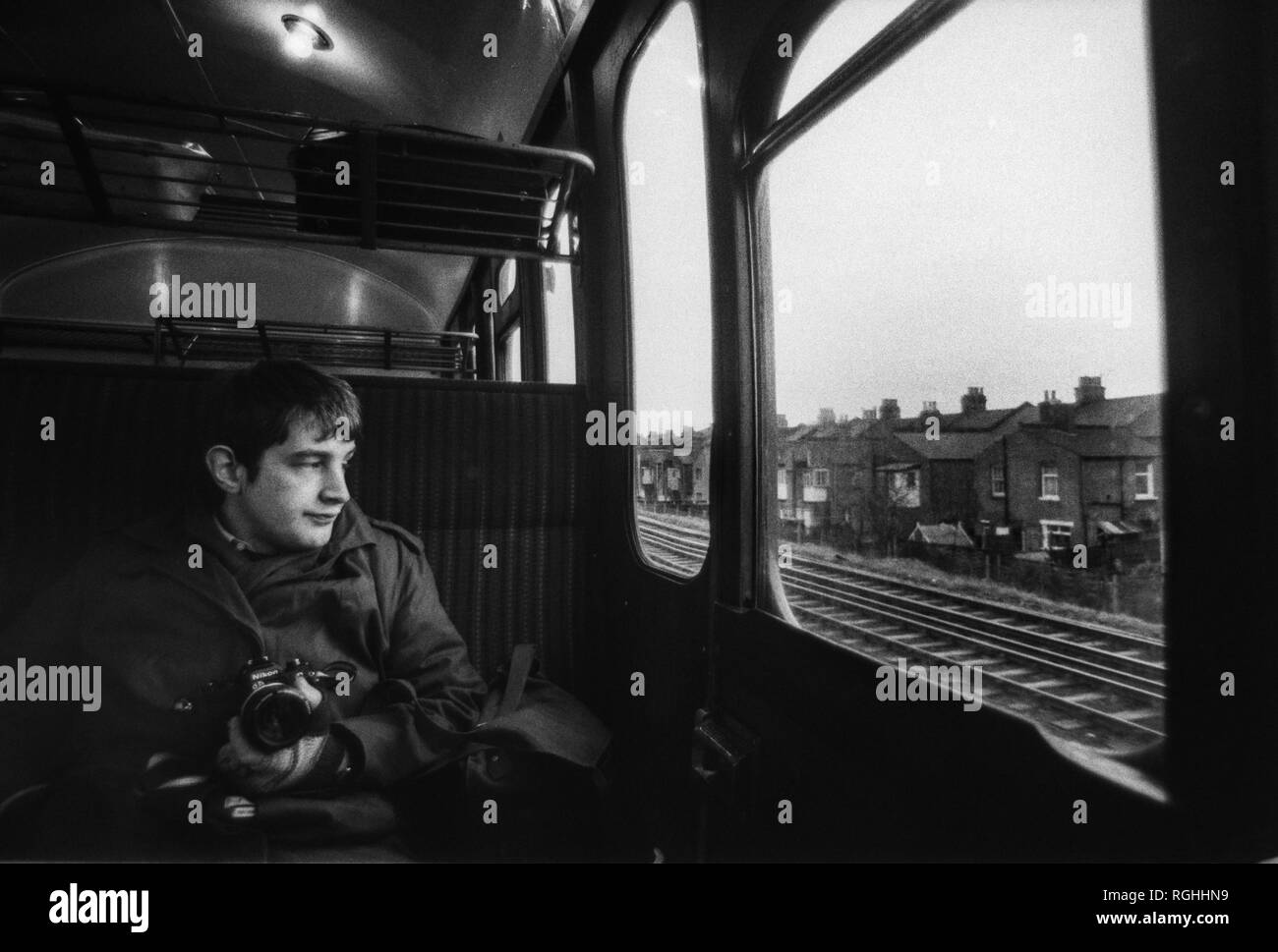 Archive image of a photographer with Nikon SLR camera looking out of the window of a British Rail slam door train on a suburban south London line, 1979, London, England - Stock Image