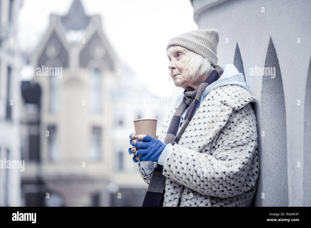 Sad aged woman standing at the corner of a building - Stock Image