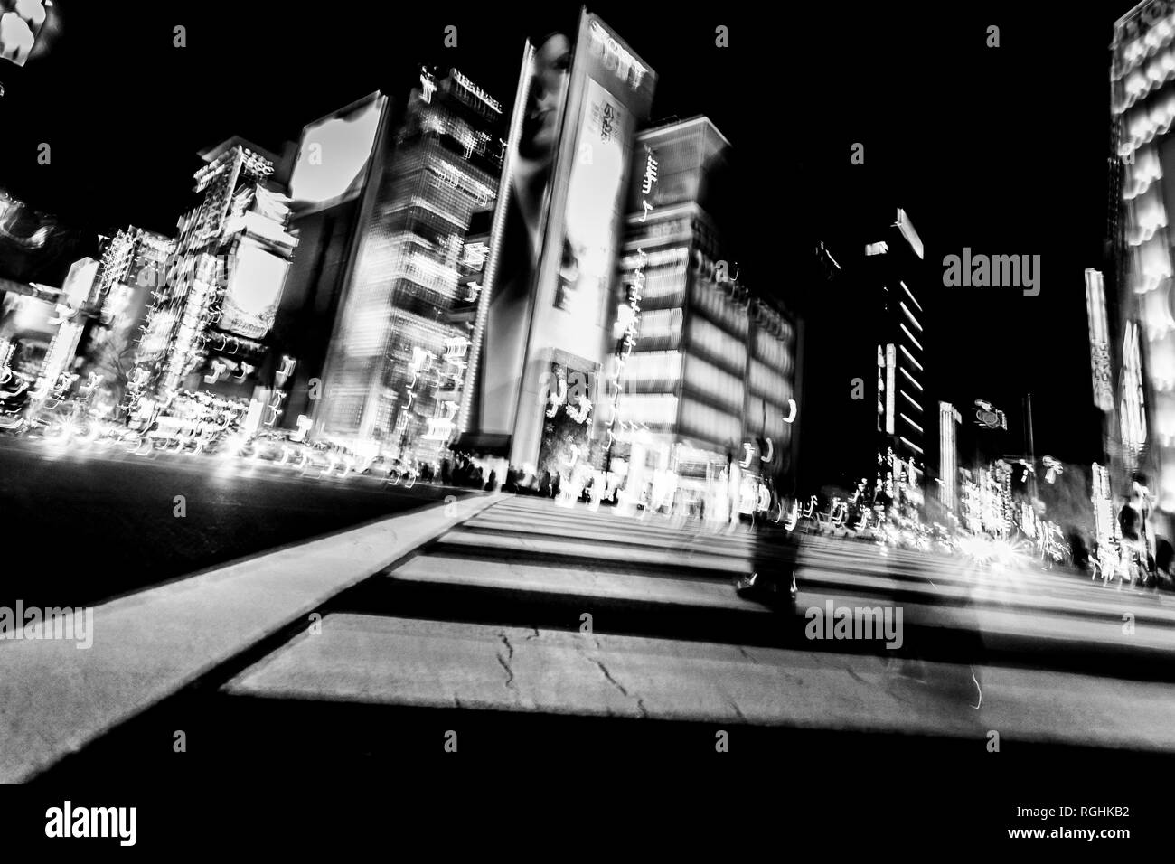 Pedestrians cross the street at the heart of Ginza District in Tokyo. Ginza crossing at night. Blurred motion, black and white image. Stock Photo