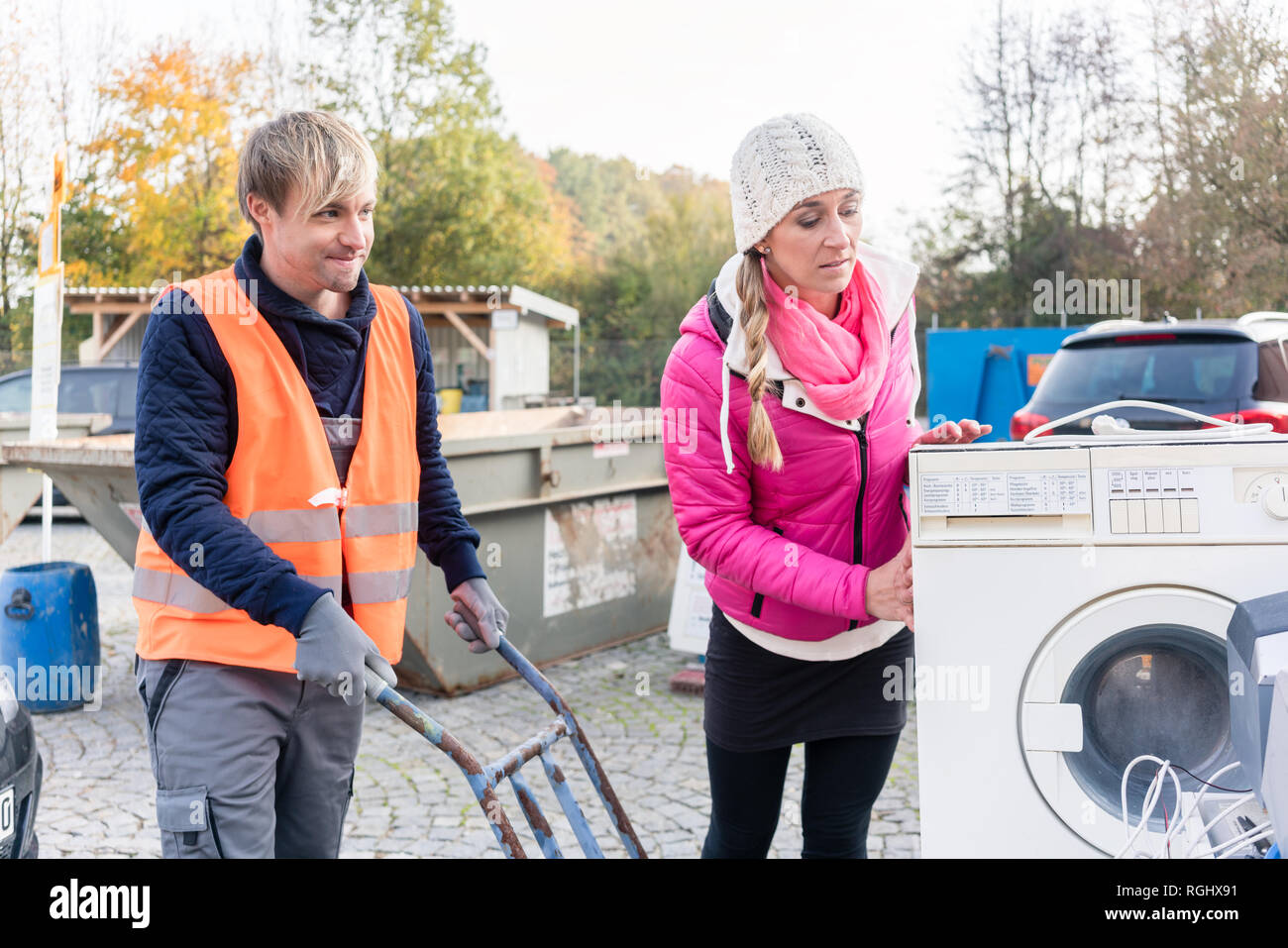Woman and man giving electrical appliances to recycling center Stock Photo