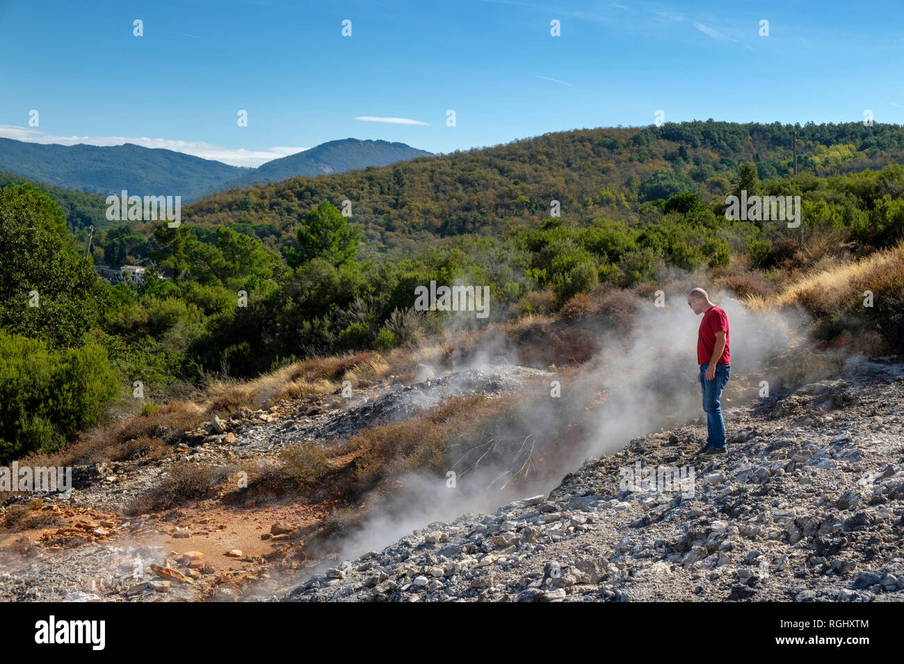 Italy, Tuscany, Colline Metallifere, Val di Cecina, Sasso Pisano, Valle delle Diavolo, hiker looking at geothermal field - Stock Image