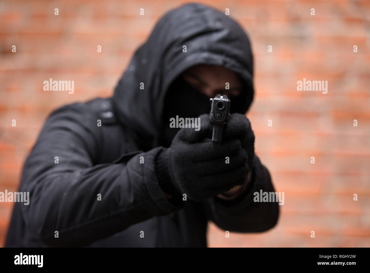 Man in black mask with handgun. Criminal and terrorism concept - Stock Image
