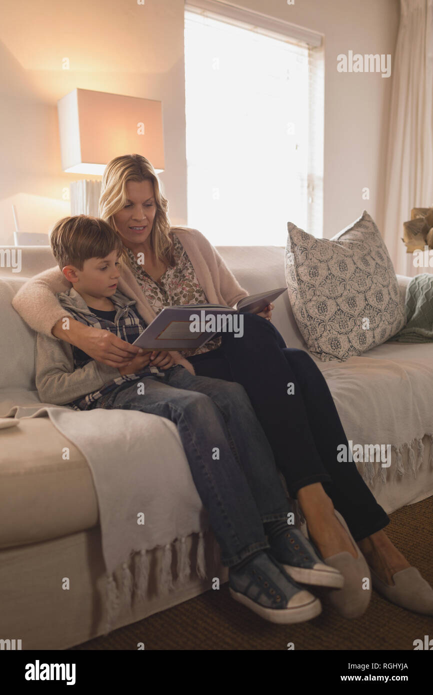 Side view of attractive mother with her son spending time together while reading story book in living room at home Stock Photo