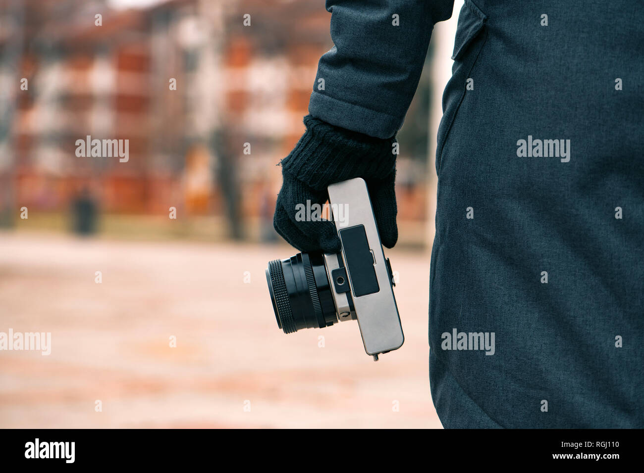 Hipster female photographer holding vintage SLR camera on street in winter, close up of hand - Stock Image