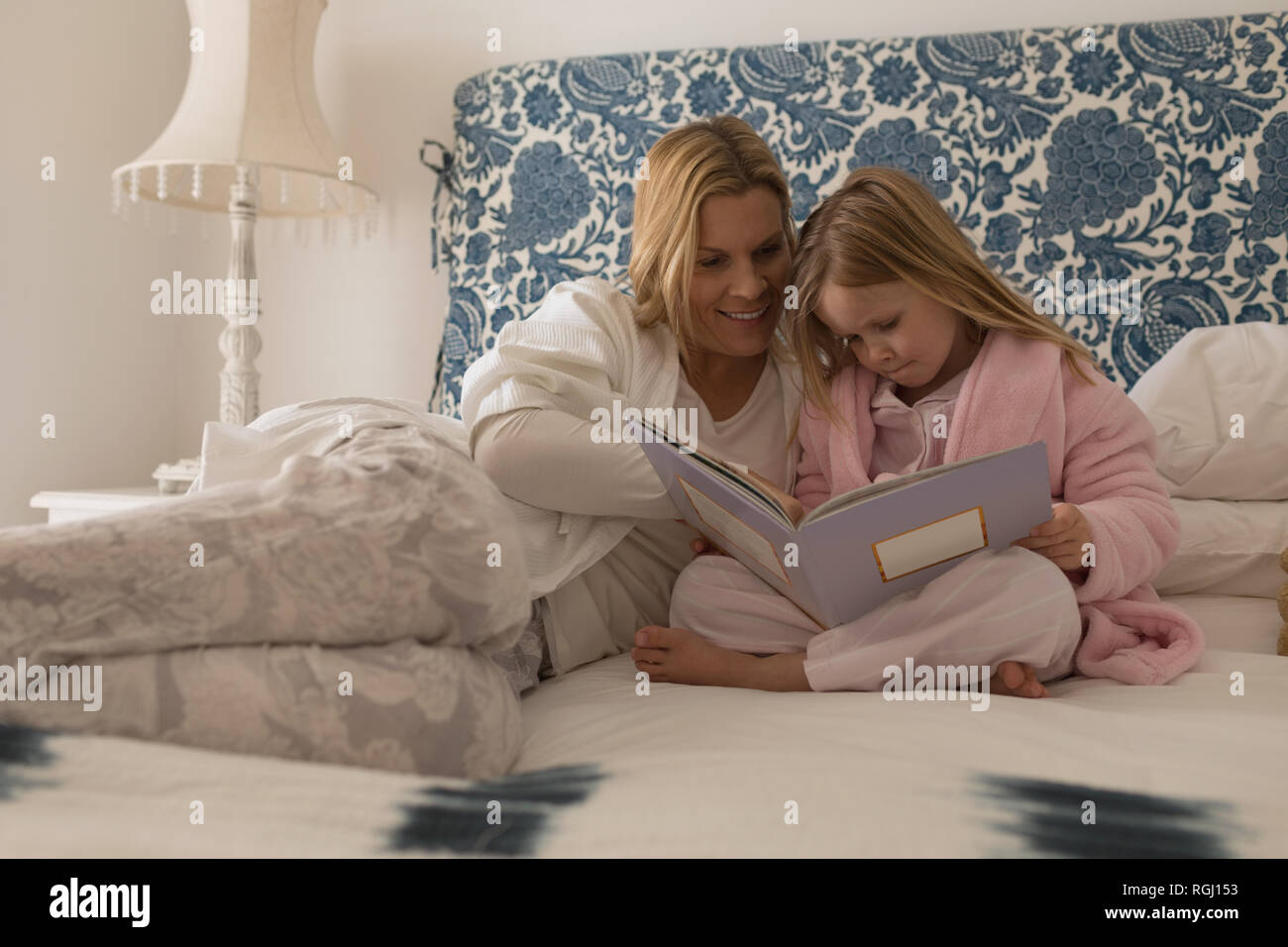 Front view of happy mother with her daughter reading storybook in bedroom at home - Stock Image