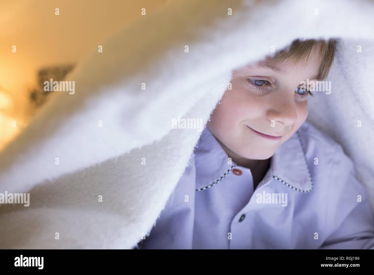 Boy relaxing under blanket in bedroom at home - Stock Image