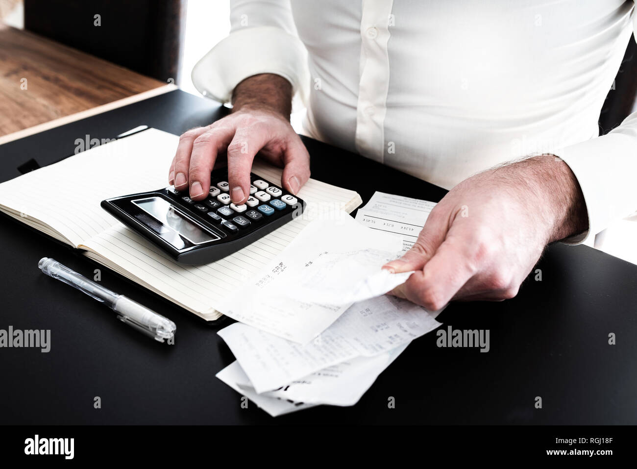 man at desk with calculator, bills or sales slips and notpad - Stock Image