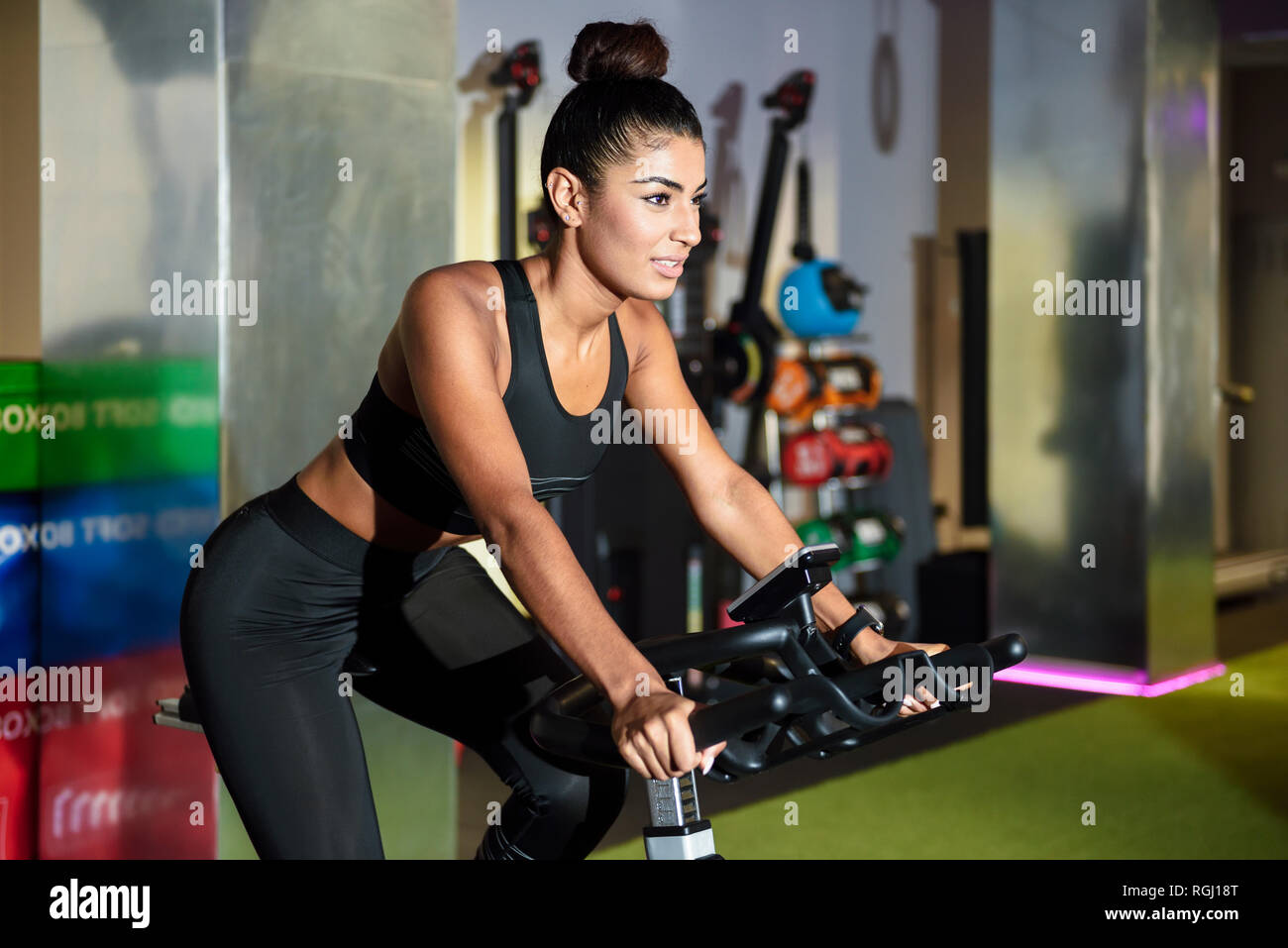 Woman on spinning bike in a gym - Stock Image