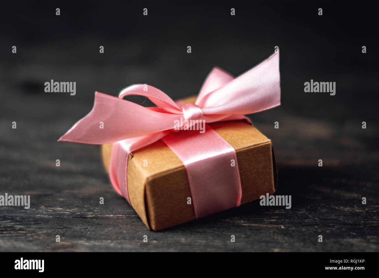 Holiday gift box Packed in crafting paper and red polka dots on dark wooden background. The concept of beautiful cards with gifts - Stock Image