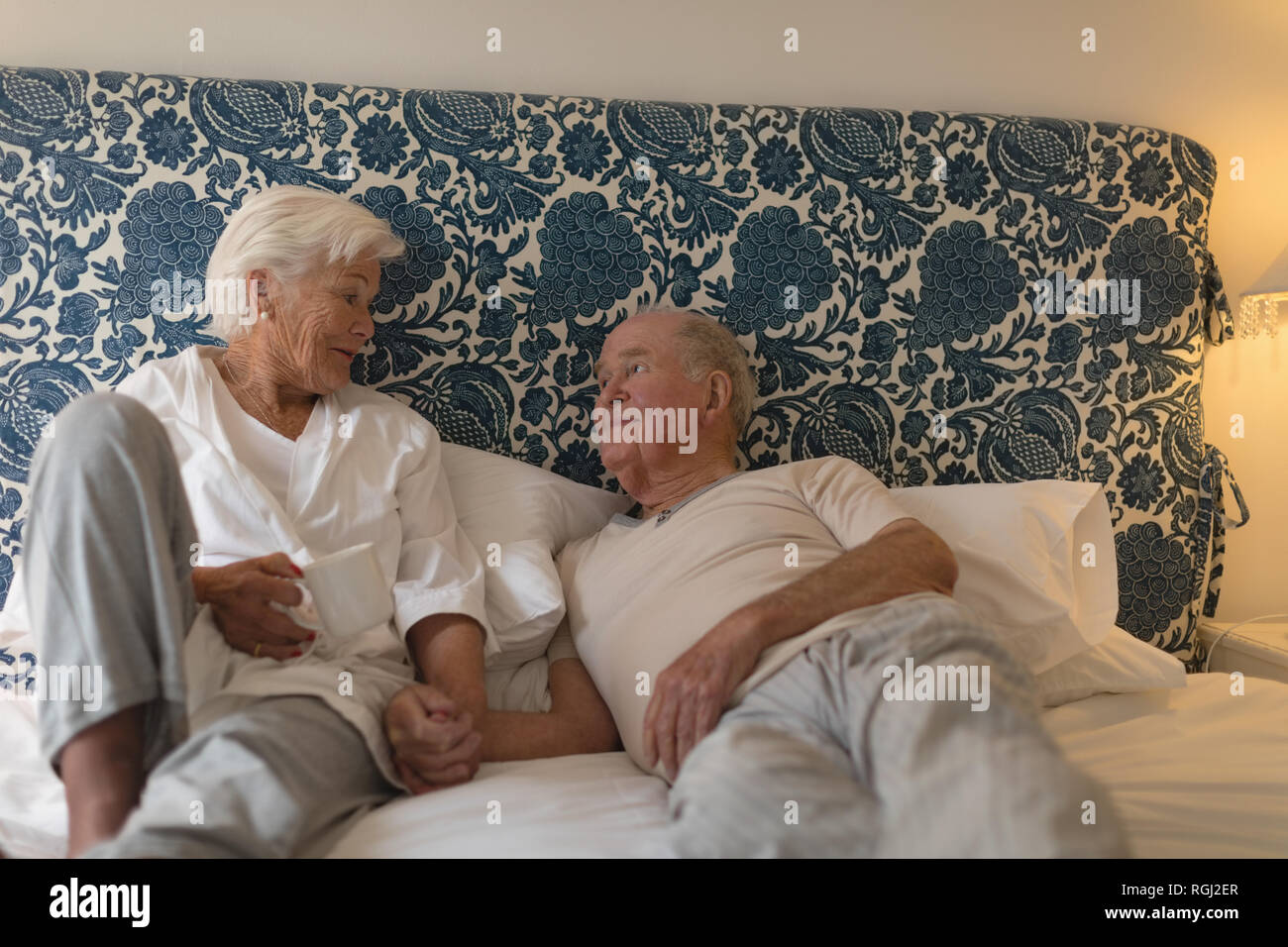 Front view of a senior couple interacting and looking each other in bedroom at home - Stock Image