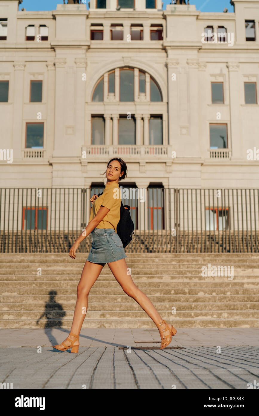Spain, Barcelona, Montjuic, portrait of young woman passing a building - Stock Image
