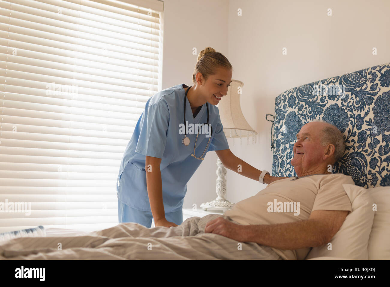 Front view of a female doctor interacting with a senior man lying on bed at home - Stock Image