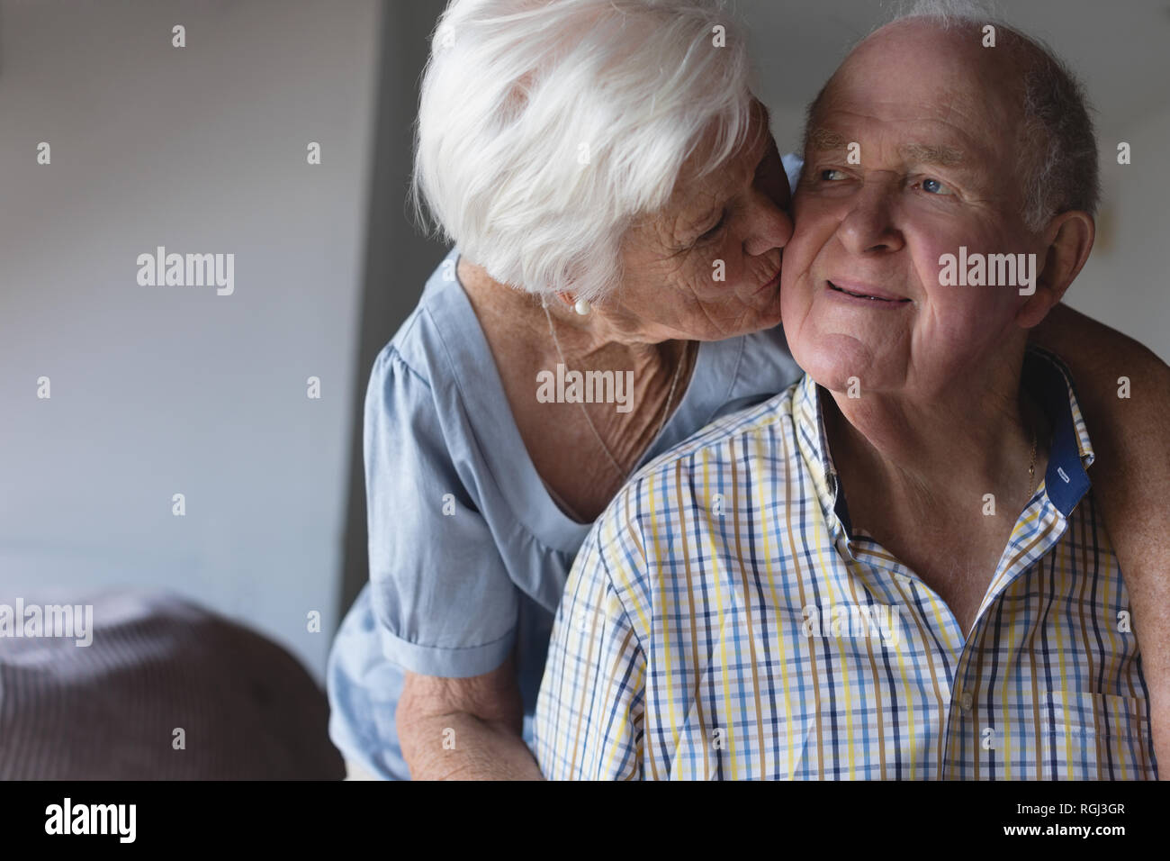 Front view of an active senior woman kissing senior man on the cheek at home - Stock Image
