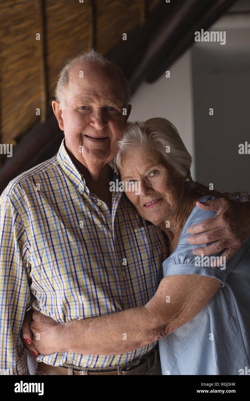 Portrait of  an active senior couple standing and embracing each other at home - Stock Image