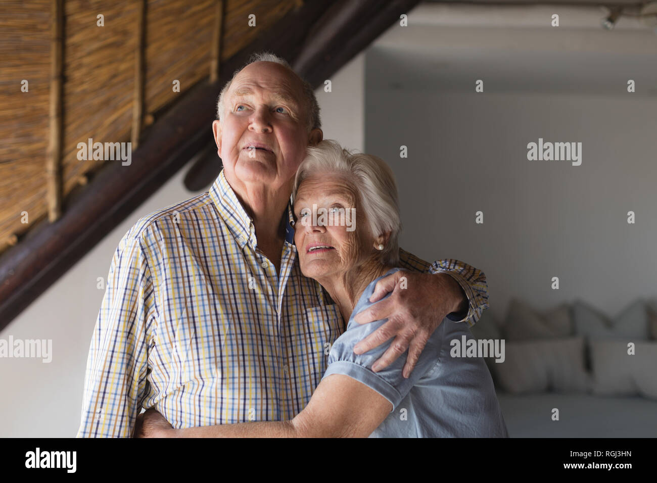 Front view of an active senior couple standing and looking away while embracing each other at home - Stock Image