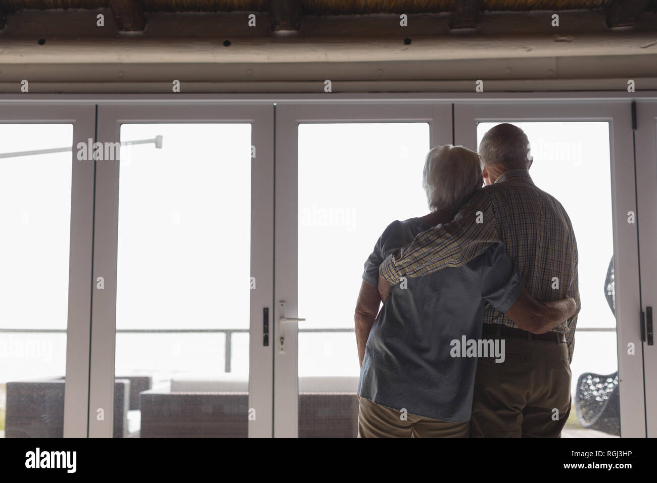 Rear view of active senior couple standing together while looking through the window at home - Stock Image