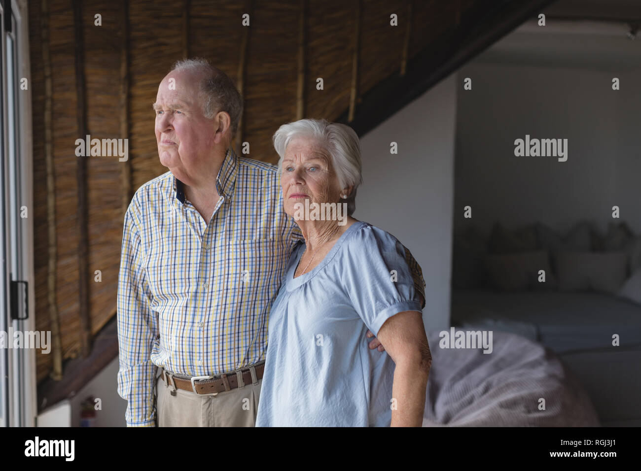 Side view of an active senior couple standing together and embracing each other while looking away at home - Stock Image