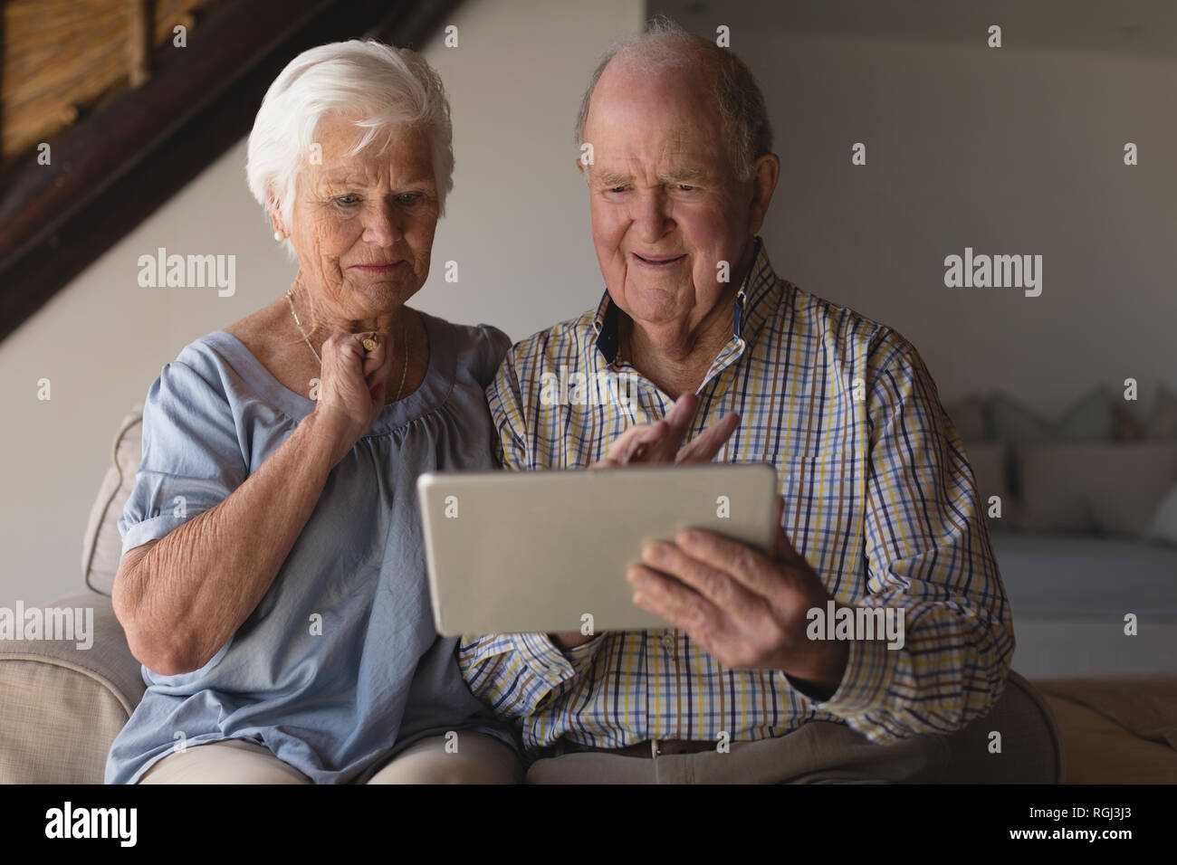 Front view of a senior couple using digital tablet in living room at home - Stock Image