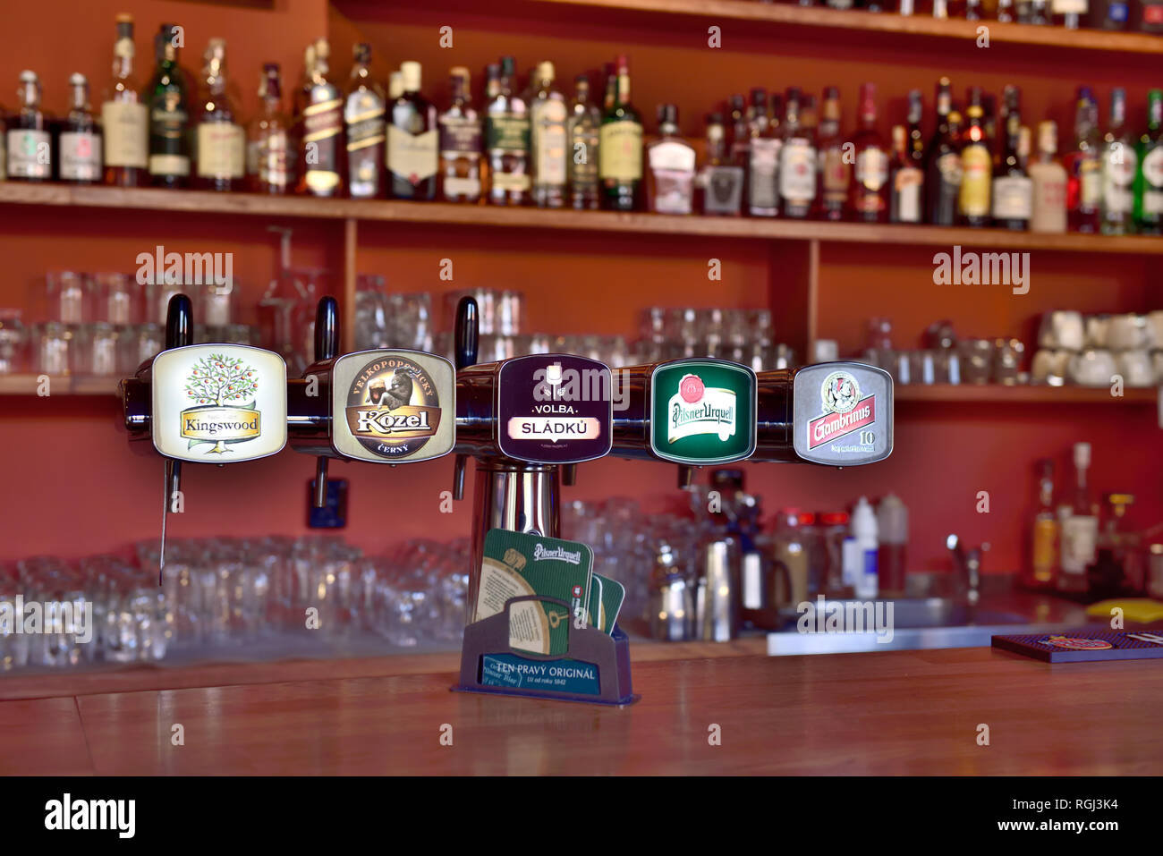 Beer taps in Prague bar with glasses and spirit bottles in background - Stock Image