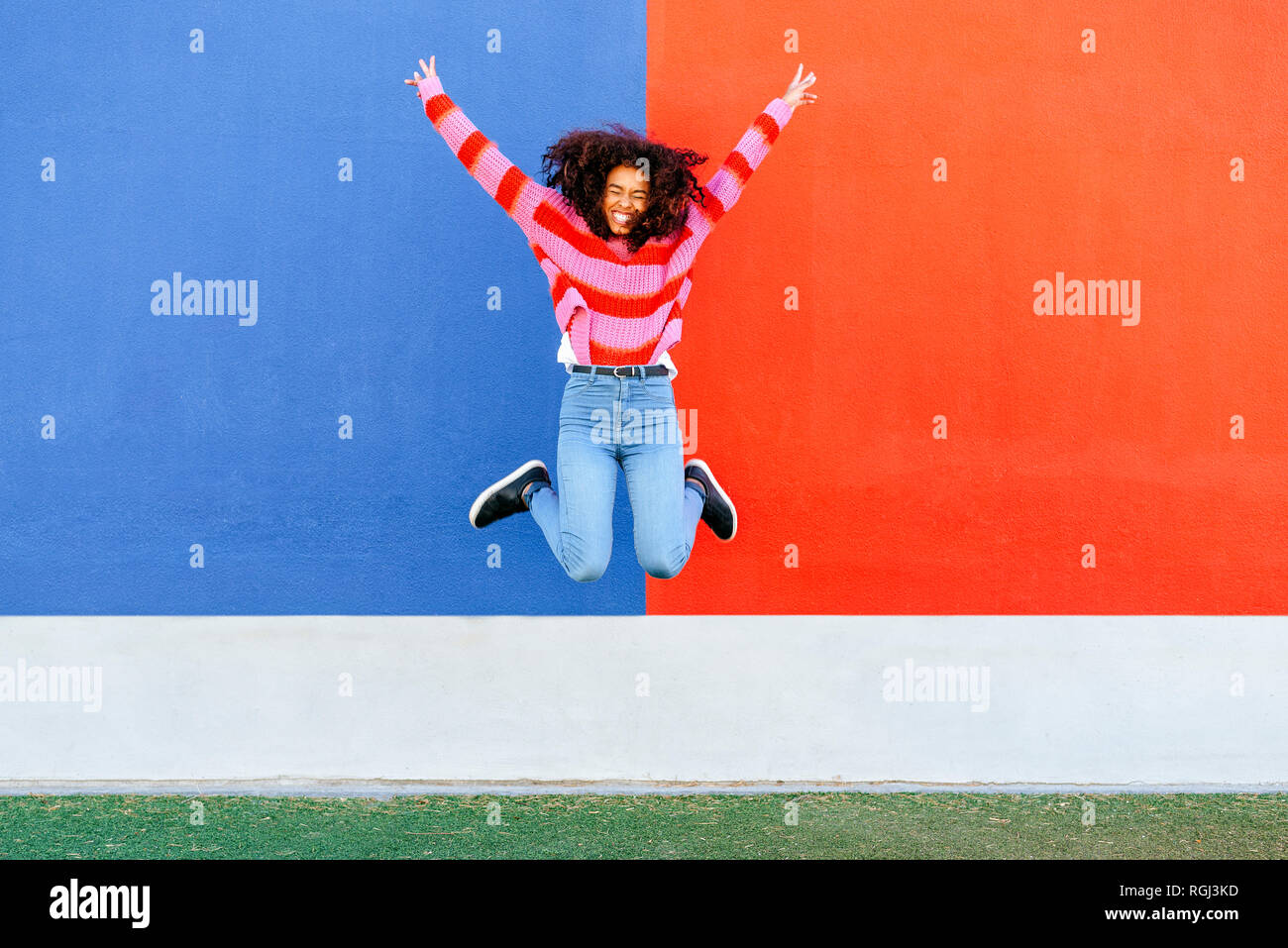 Happy young woman jumping in the air Stock Photo