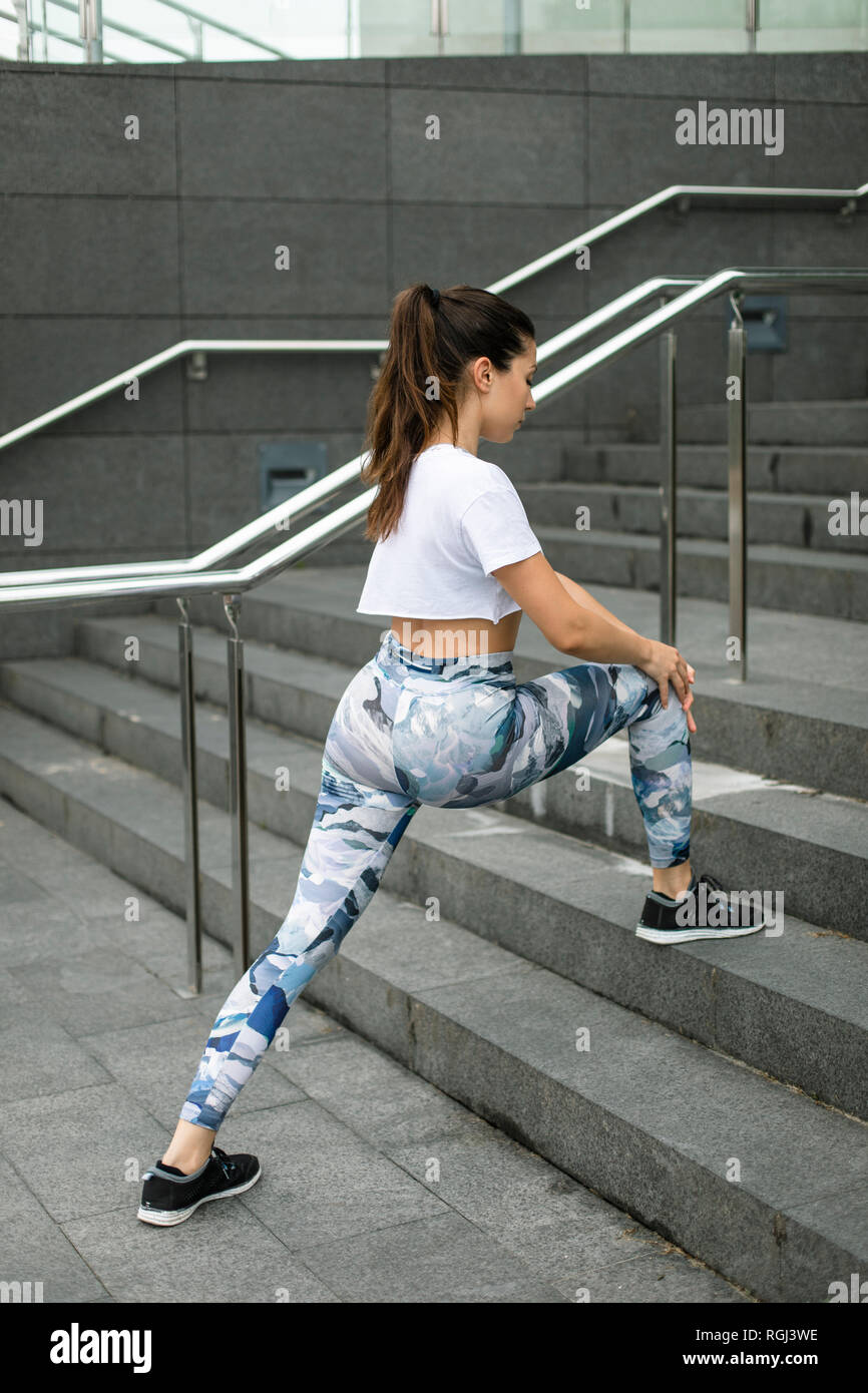 Young woman doing stretching exercise on stairs - Stock Image