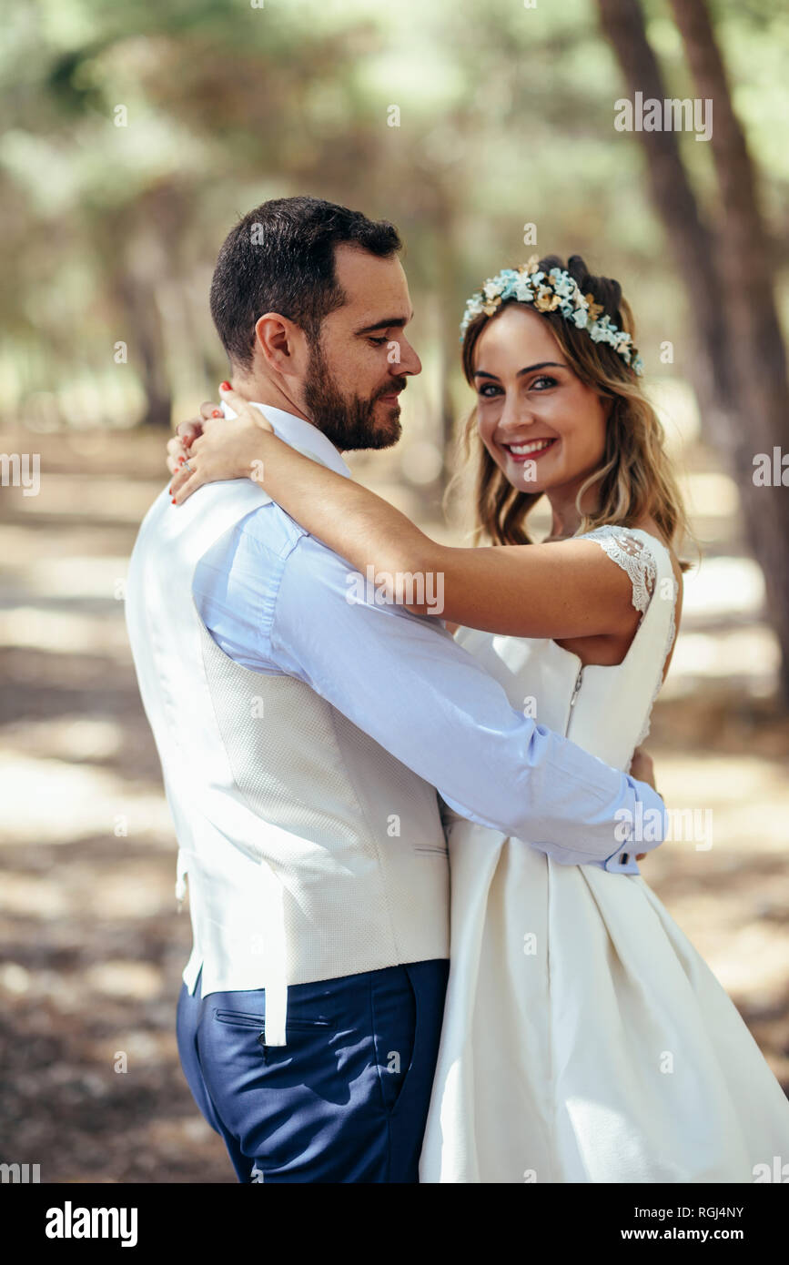 Portrait of happy bride dancing with her groom in pine forest - Stock Image