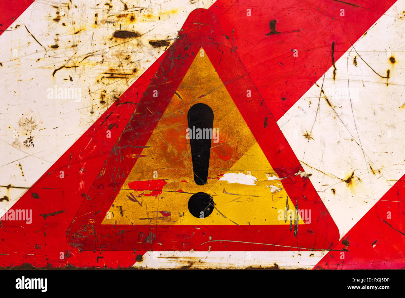 Exclamation triangular road sign for other danger, damaged and weathered surface - Stock Image