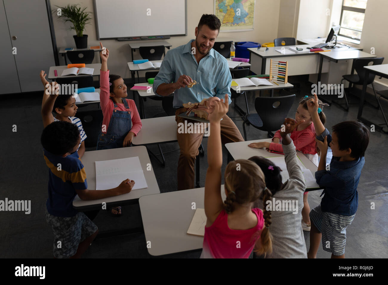 High angle view of school kids raising hands while teacher studying in classroom of elementary school Stock Photo