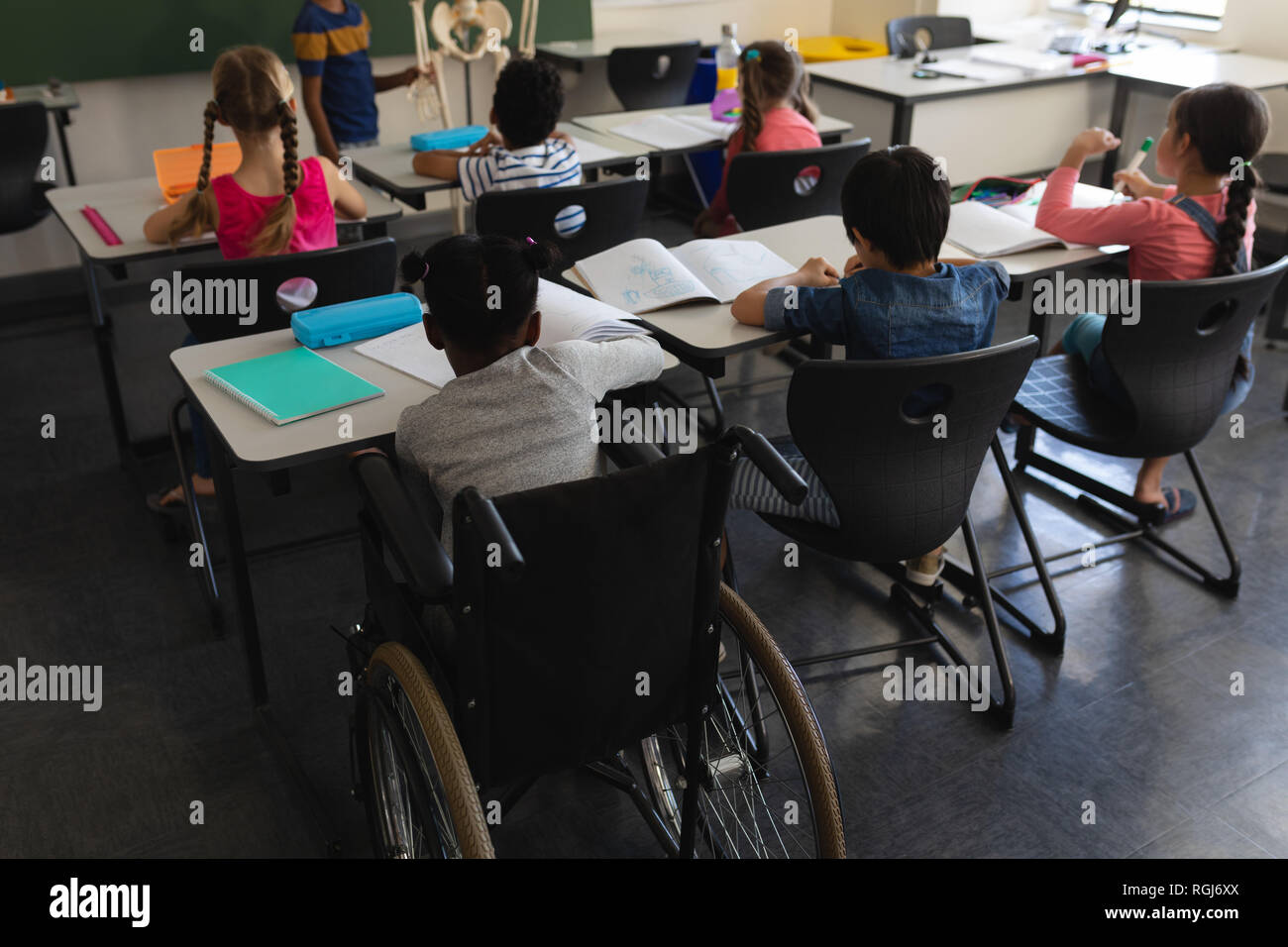 Rear view of disable schoolboy with classmate studying and sitting at desk in classroom of elementary school - Stock Image
