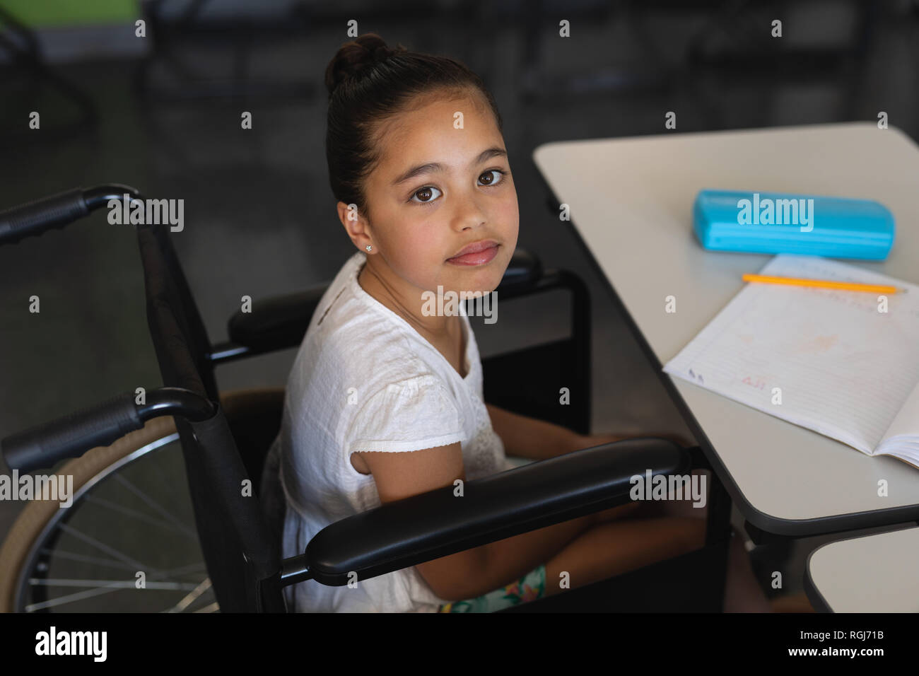 High angle view of disabled schoolgirl looking at camera and sitting at desk in classroom - Stock Image