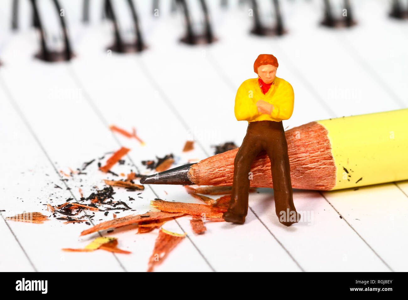 Conceptual diorama image of a miniature figure with writers block sat on a pencil on a note book - Stock Image