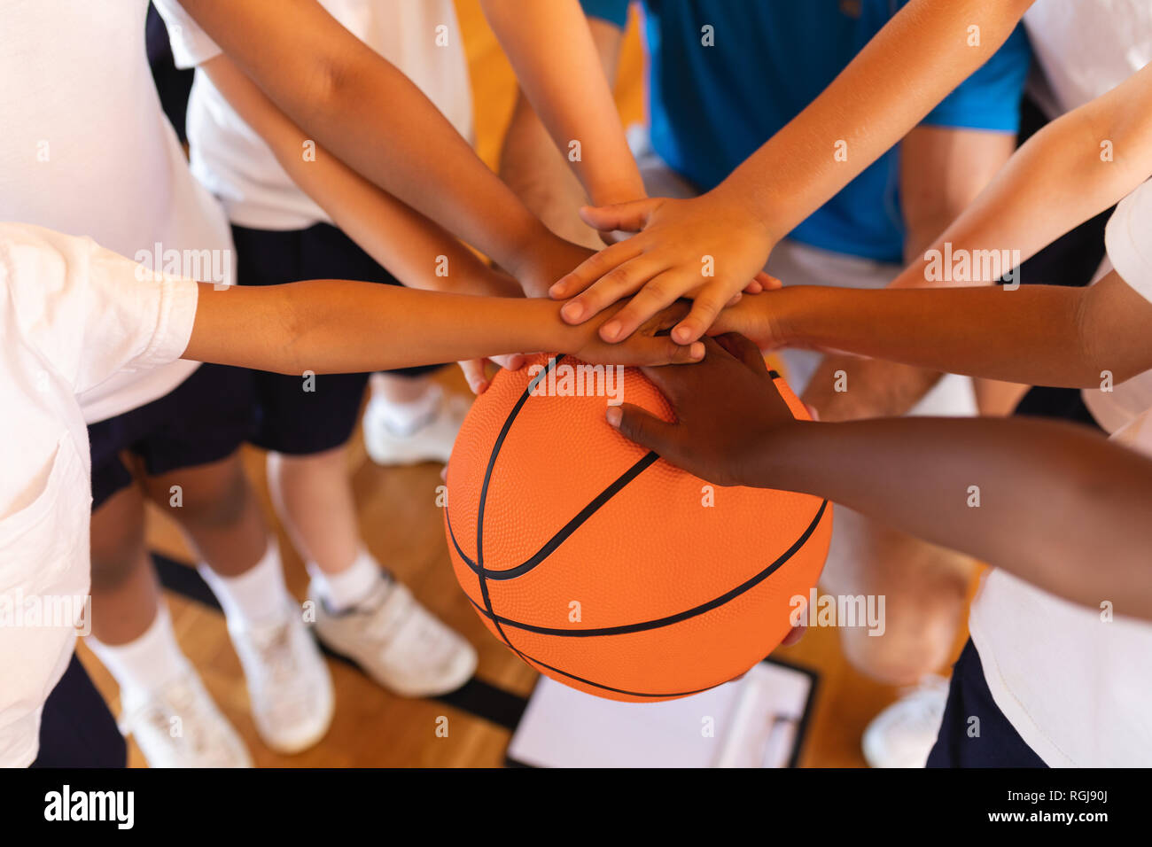 Close-up of Schoolkids forming hand stack on basketball at basketball court in school Stock Photo