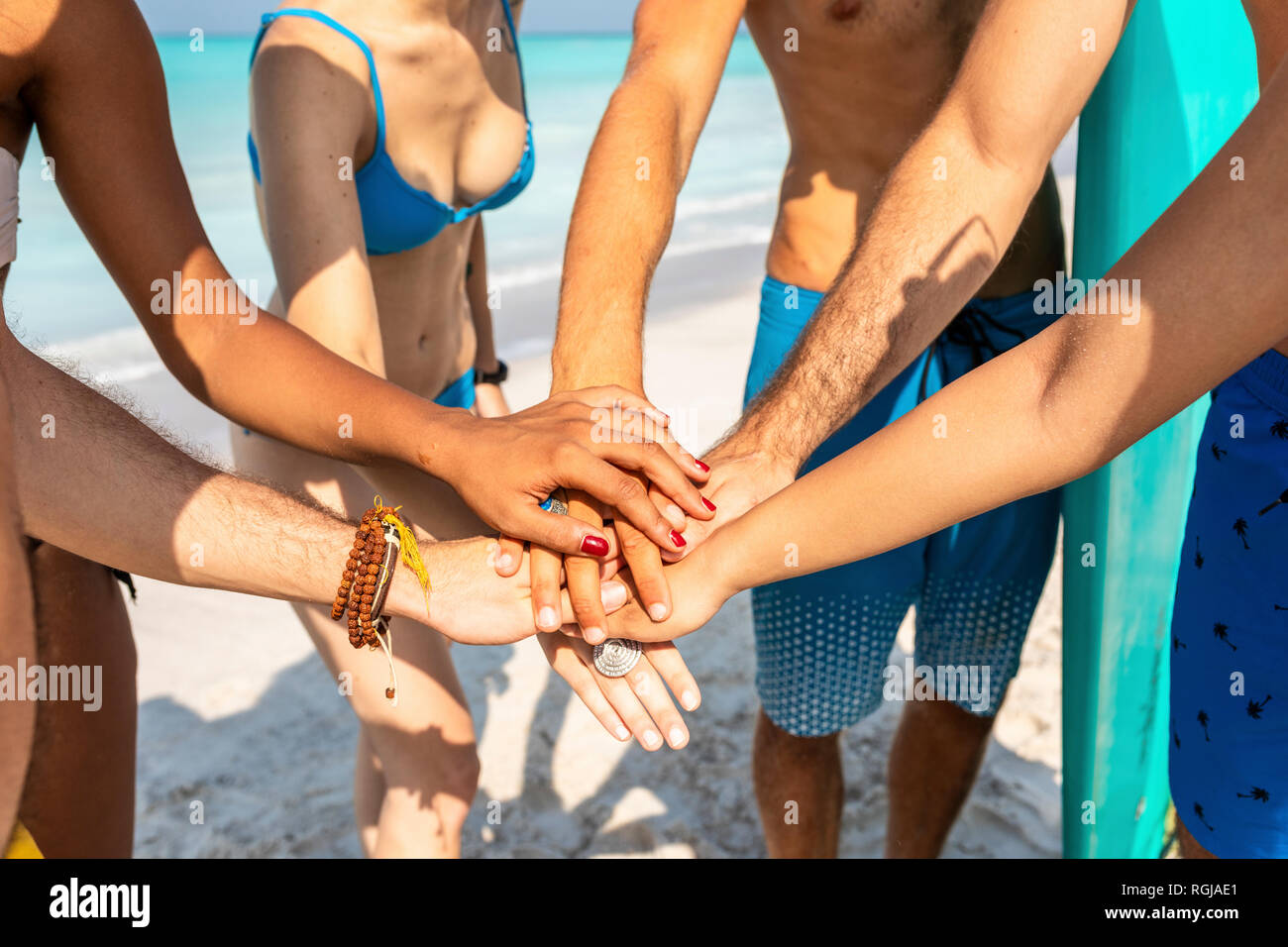 Group of friends on the beach stacking hands - Stock Image