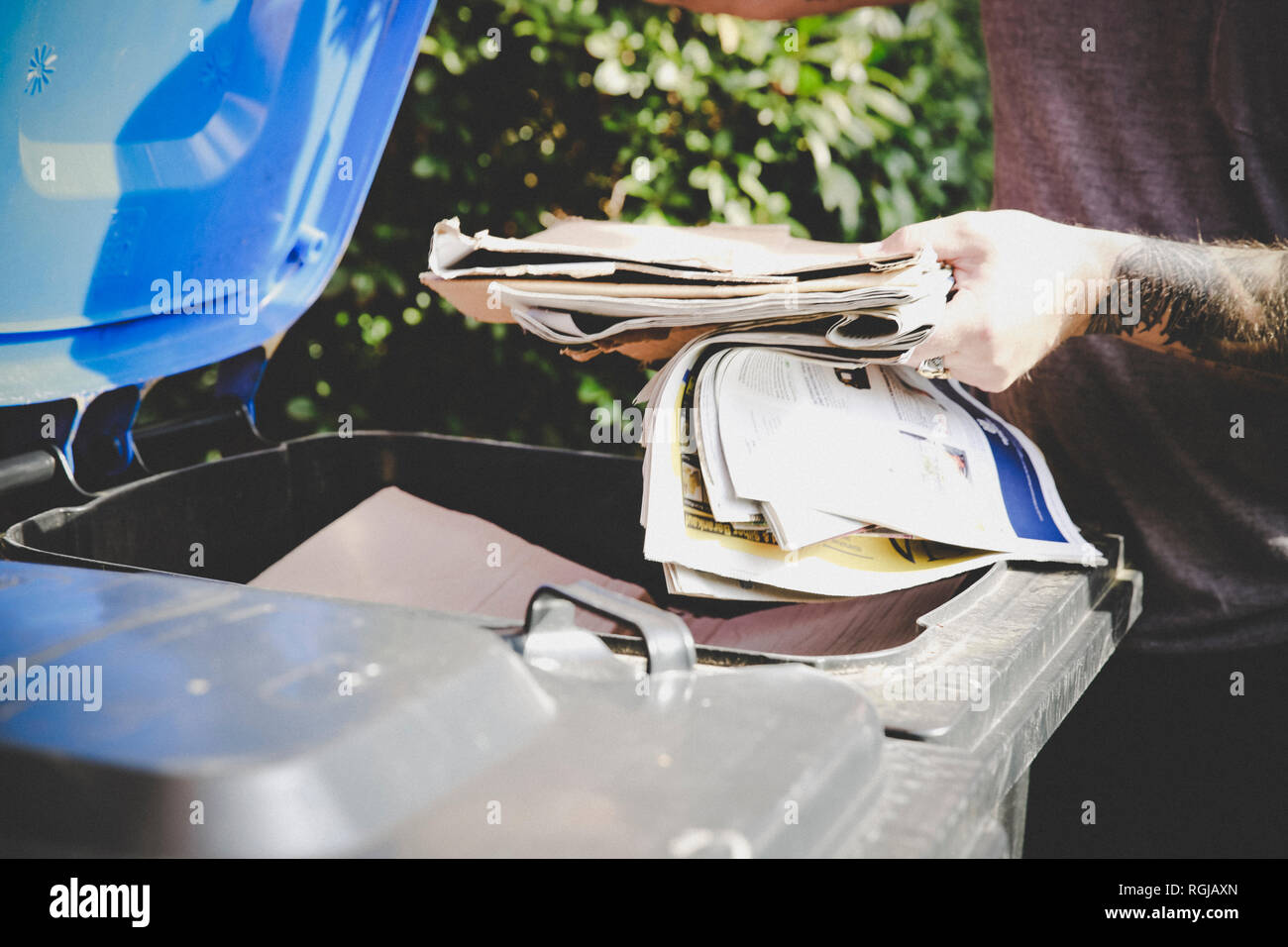 Tattooed man recycling waste paper in paper bank, partial view Stock Photo