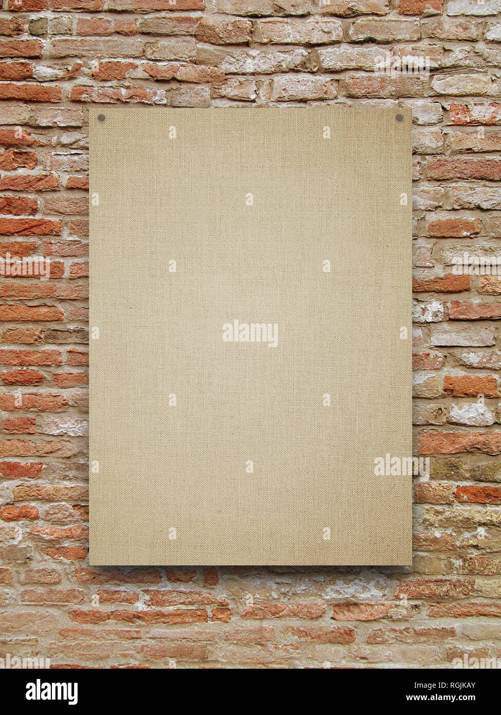 Blank canvas frame on orange weathered brick wall background - Stock Image
