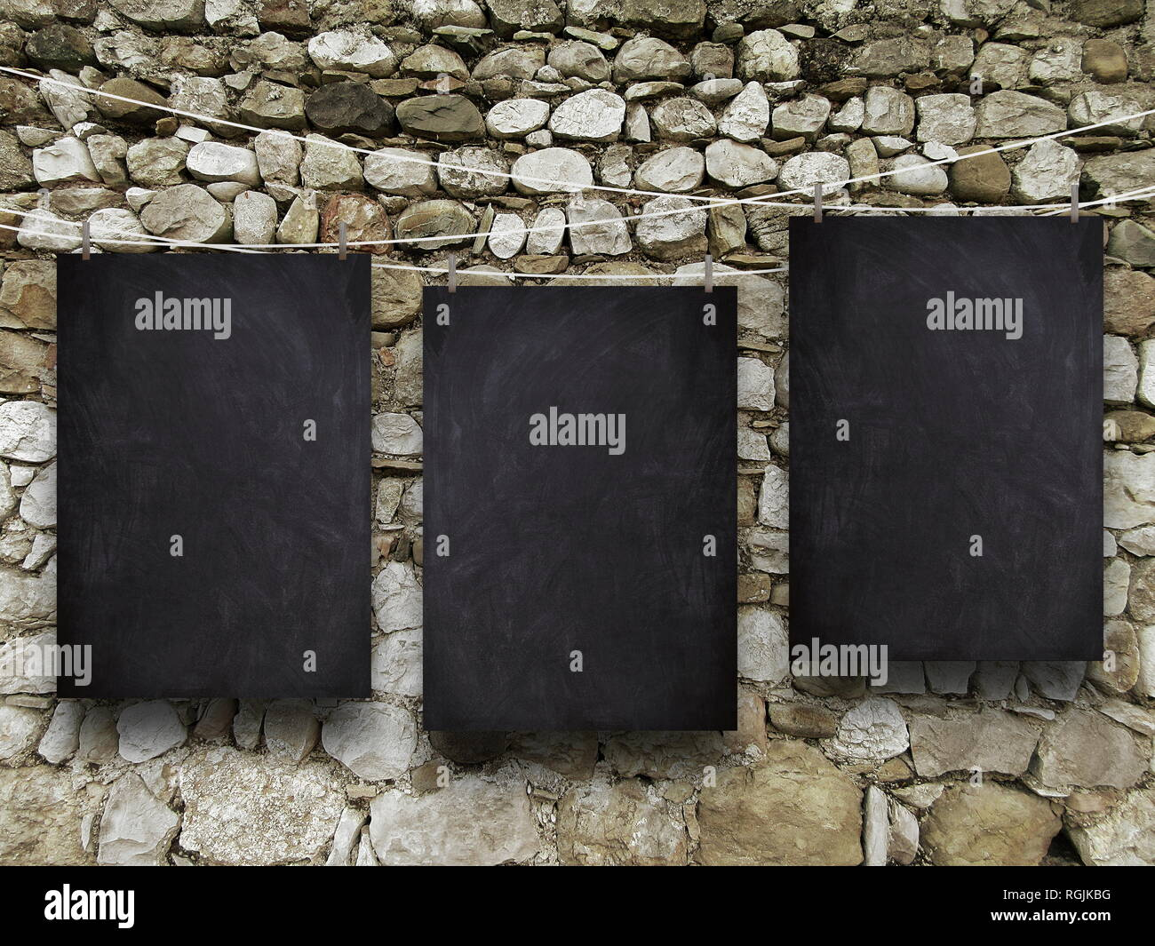 Three blank blackboard frames against old stone wall background - Stock Image