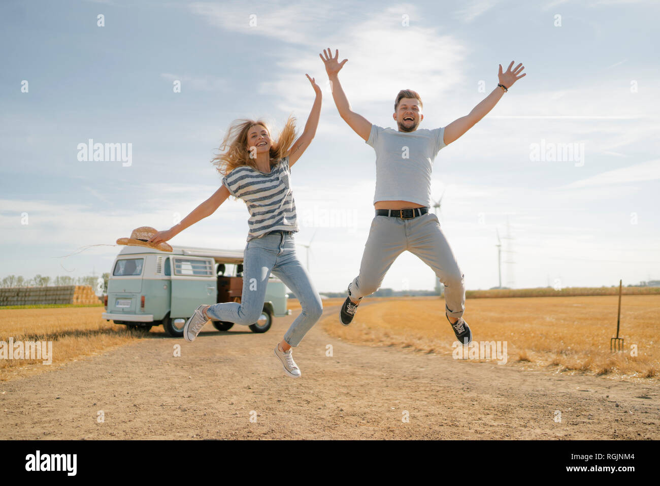 Exuberant couple jumping on dirt track at camper van in rural landscape Stock Photo