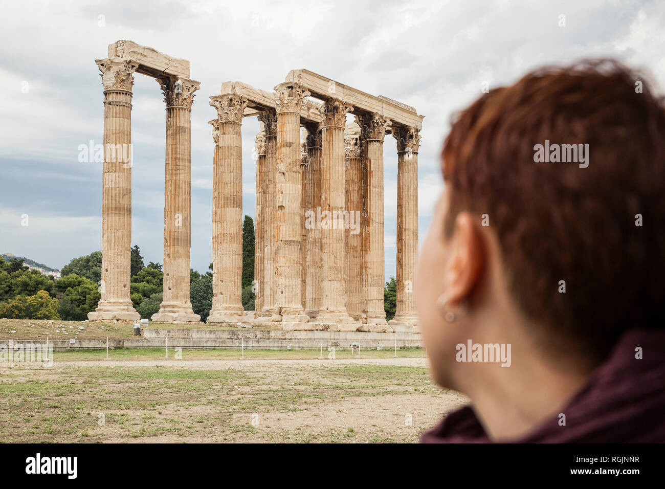 Greece, Athens, Olympeion, Woman looking at Temple of Zeus - Stock Image