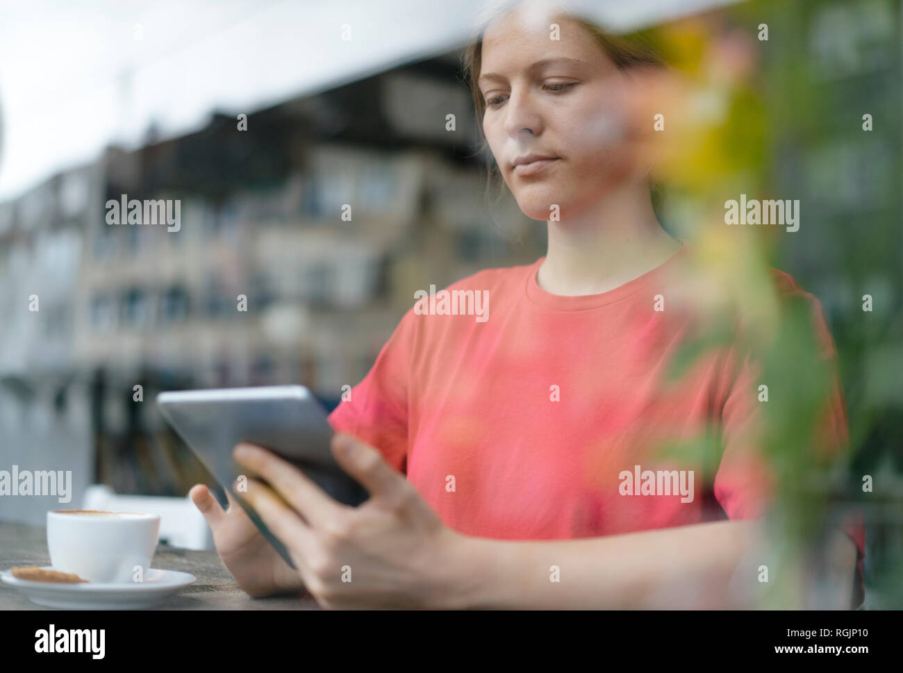 Young woman using tablet at the window in a cafe - Stock Image