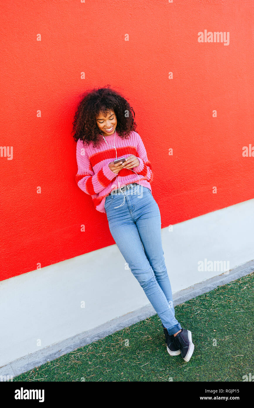 Smiling young woman with earphones leaning against red wall looking at cell phone Stock Photo