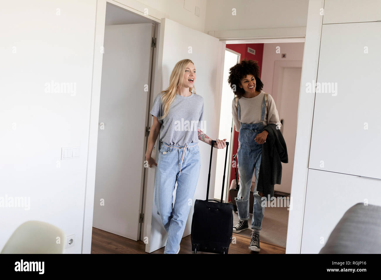 Two happy women with baggage arriving in accomodation - Stock Image