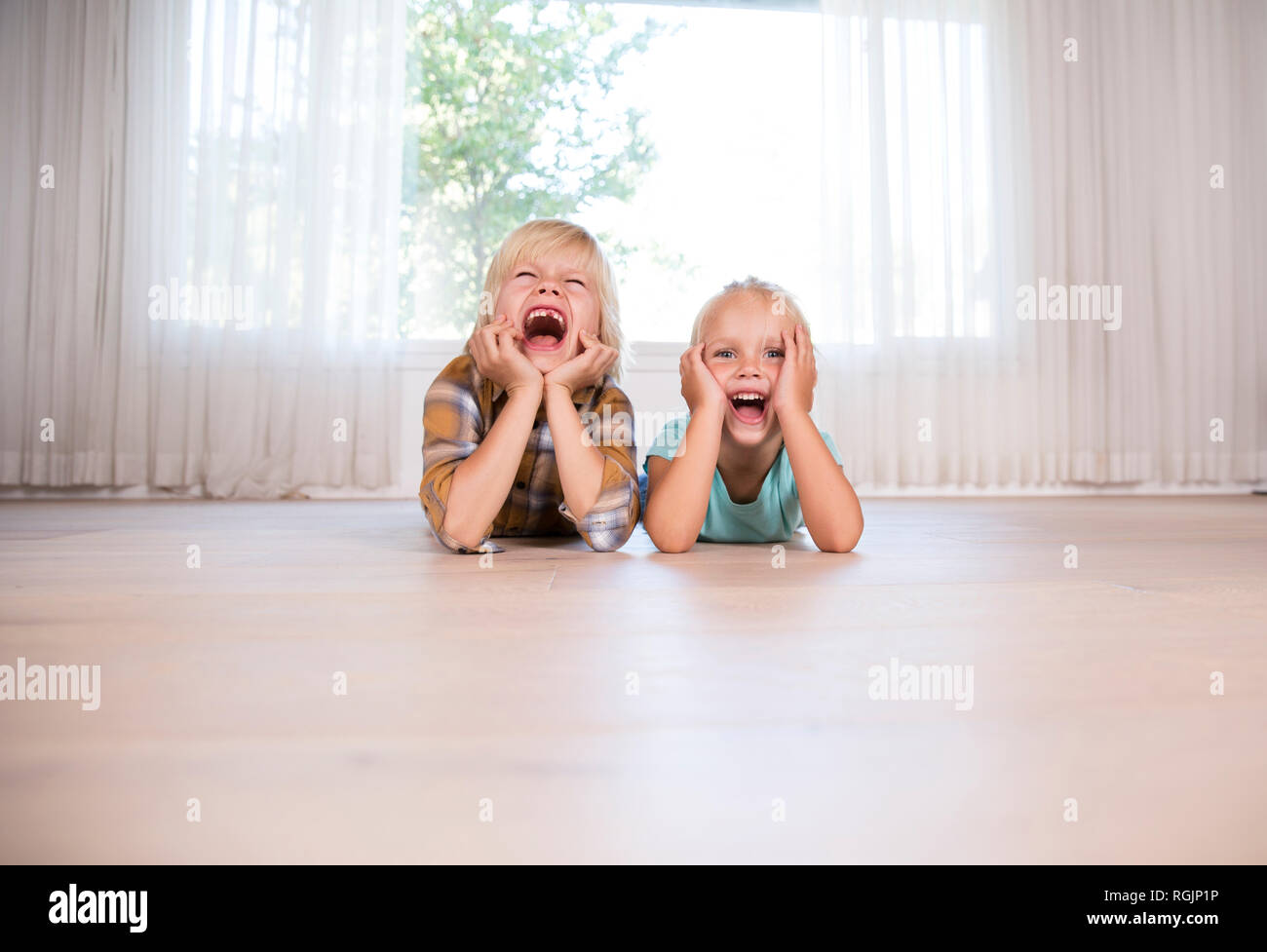Brother and sister lying on the floor at home grimacing - Stock Image
