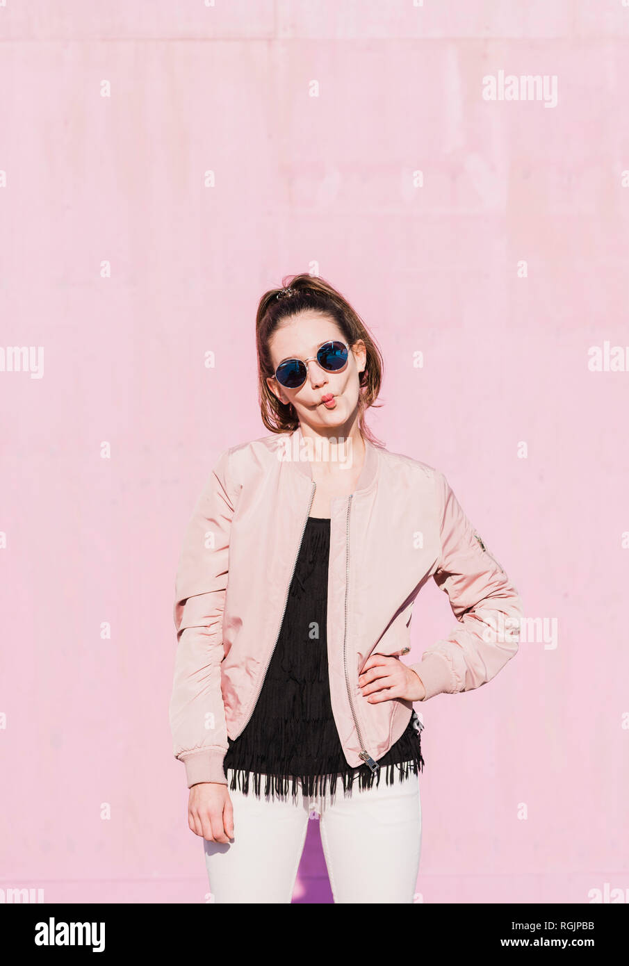 Portrait of young woman wearing sunglasses grimacing in front of pink wall - Stock Image