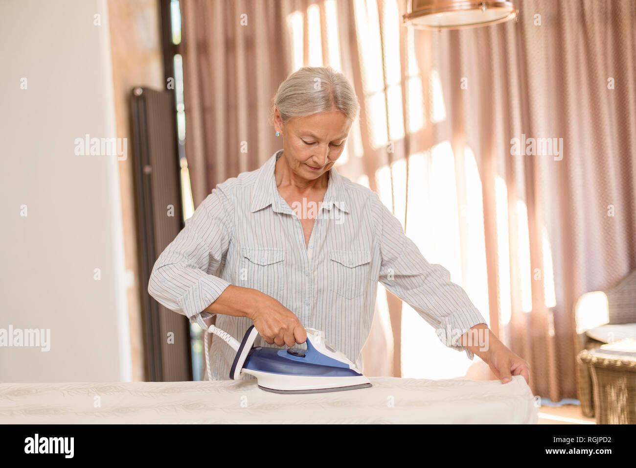 Senior woman ironing - Stock Image